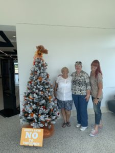 Charlotte, Erin, and Joy erect a tree at Marathon City Hall to spread the word about gender based violence.